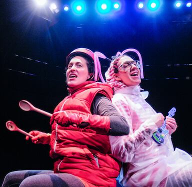 Two women sit back to back singing, one is dressed in a red body warmer and helmet, the other wears a clear raincoat.