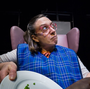 A woman with glasses looking away from the camera. She is sitting in a chair, wearing a bib, tilting a plate of food into a bag.