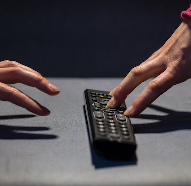 Two hands reaching for a remote control.