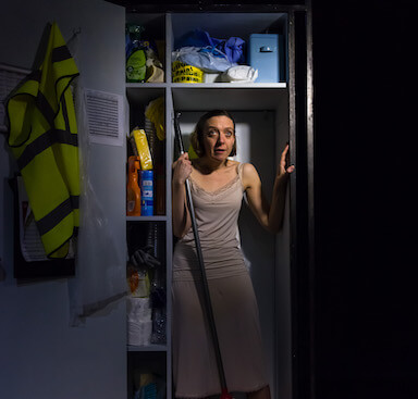 A woman in a night gown, standing inside a cleaning cupboard.