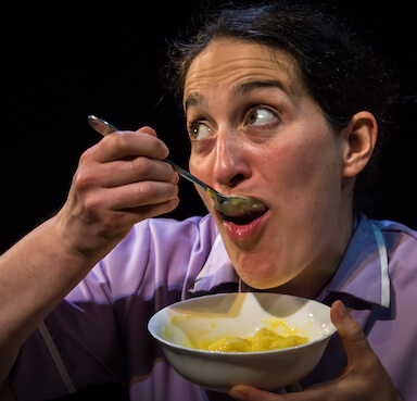 A woman eating a bowl of custard, the spoon is in her mouth and she is looking away from the camera.