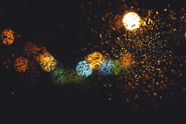 A view through a window, with rain splatters and colourful lights.