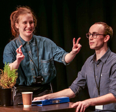 A woman gesturing quotation marks with her hands, towards a man sitting at a desk facing towards the audience.