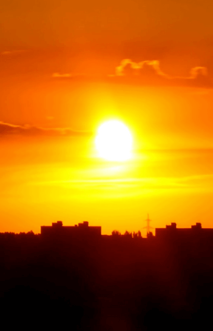 A sunset rising over the silhouette of buildings.