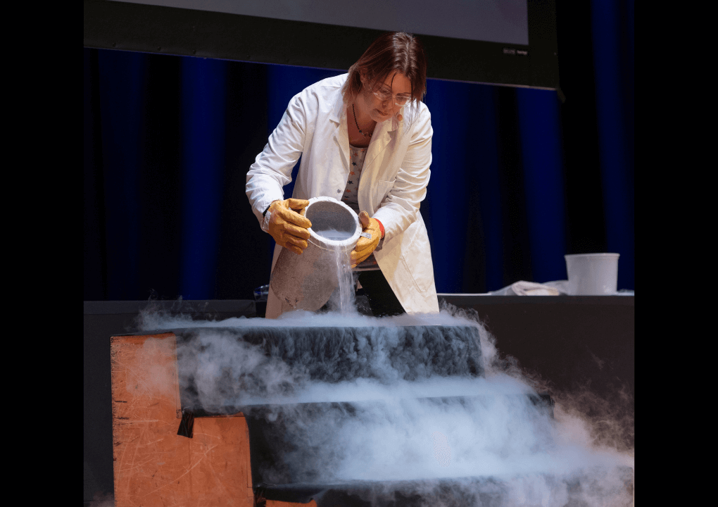 A woman pouring a liquid to create trailing smoke down some stairs, she is wearing white lab coat, safety goggles and protective gloves.