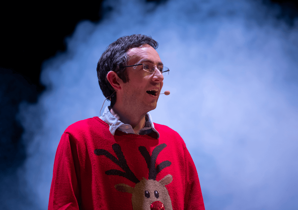 A man wearing a red reindeer Christmas jumper, looking away from the camera, he is wearing glasses and appears mid-speech.