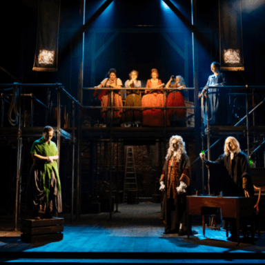 Five women looking down from a scaffolding platform and three other actors on stage.
