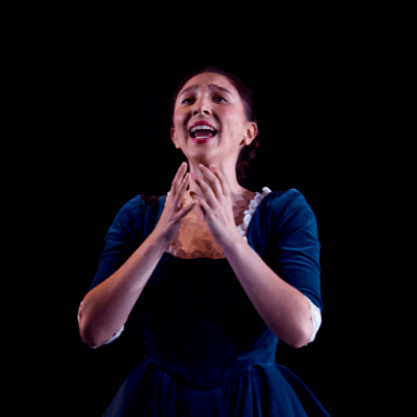 A young woman holding her arms up towards her face whilst she sings.