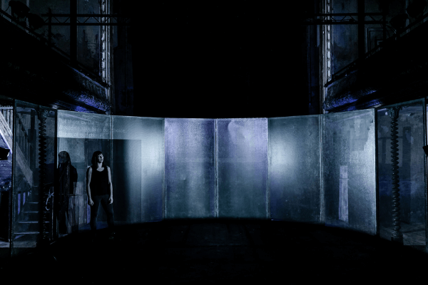 A woman standing to the left of a stage which is set in the dark with minimal lighting.