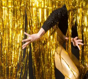 A person sticks their arm and leg through a gold tinsel curtain.