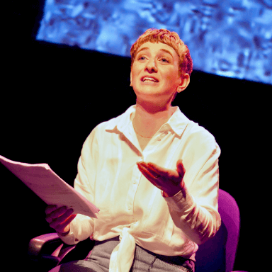 A young woman sits in an office chair, holding a script and looking up towards the audience.