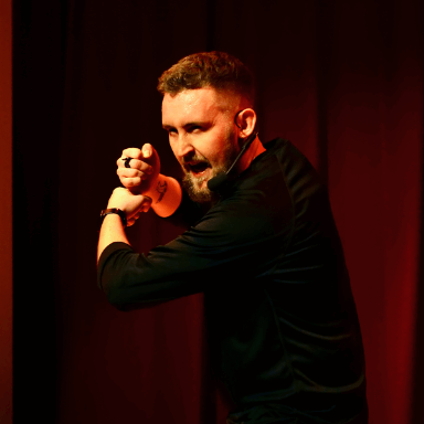 A man pretending to hold something in his hands, whilst he looks sternly at the audience.
