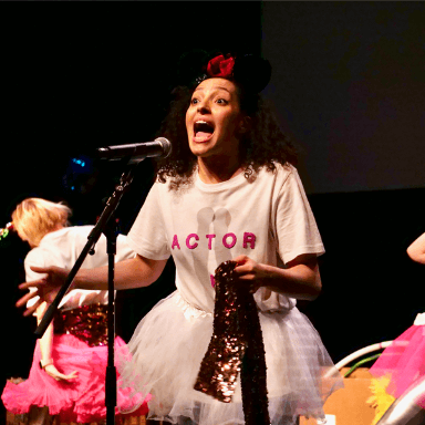 A young woman singing into a microphone, she is wearing a bow in her hair and her top says 'Actor'