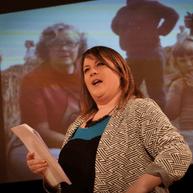 A woman holding a script, looking out to the audience, with a photograph projected behind her.