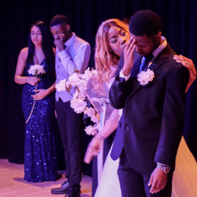 Two people stand in the background, whilst a bride stands looking at her groom who has his head down.