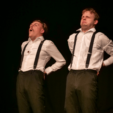 Two men wearing a white shirt, black trousers and braces, lean back with their hand on their hips pulling a face.