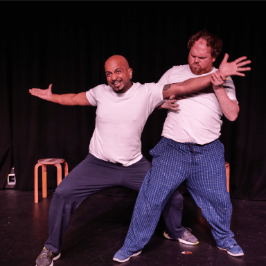 Two men performing on stage, one is standing with his arms out, whilst the other appears to block him.