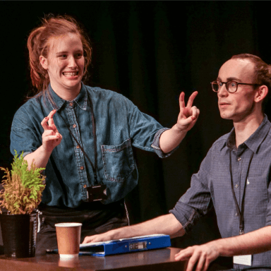 A man sits holding the edge of a table, as he looks out to the audience with concern, whilst a woman stands next to him doing inverted commas with her hands.