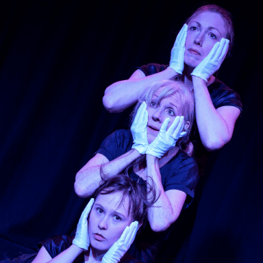 Three women rest their hands above the others head, each one is wearing white gloves.