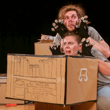 Two people wearing black gloves, crouching down and pulling a face towards the audience, in front of them is a cardboard prop.