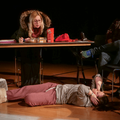 Two women performing on stage, one is sat at a table, the other lies on the floor below.