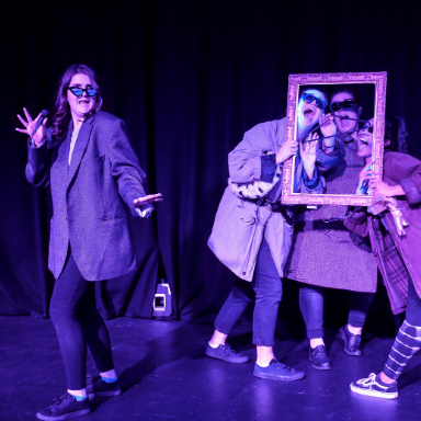 A group of people wearing jackets and sunglasses, holding poses through a frame, one stands off to the left.