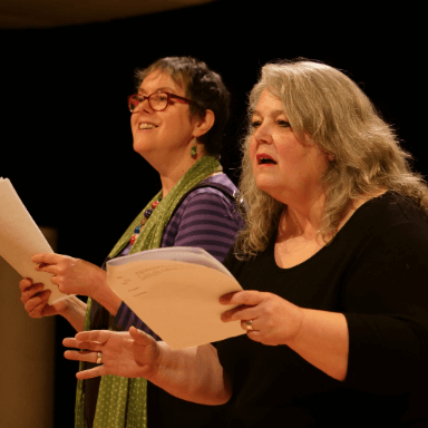 Two women reading from scripts, looking out towards an audience.