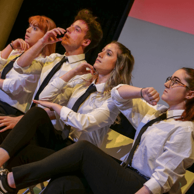 Four young people sitting on chairs facing the audience, wearing black trousers, white shirt and a black tie, each gesturing with their arm.