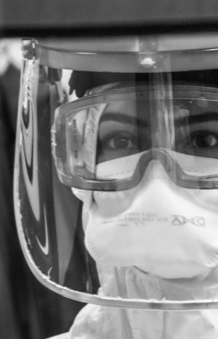 A black and white photograph of a persons face behind a plastic shield and glasses, dressed in full PPE.