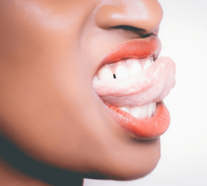 A close up of a woman biting her tongue in between her teeth.