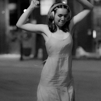 A young girl dancing in the street with headphones on.