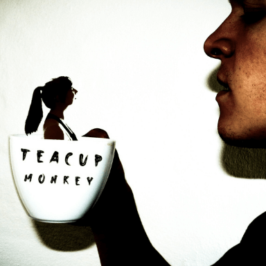 A shadow image of a girl in teacup, being held up by a hand.