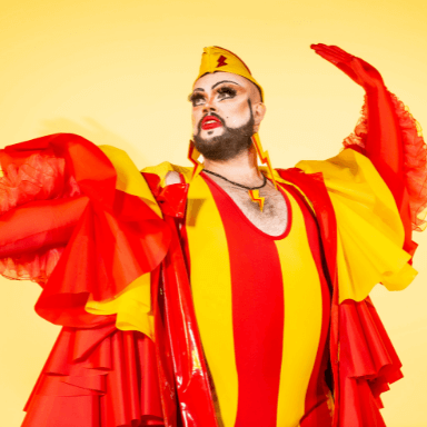 A person dressed up in drag, posing in a bright red and yellow striped outfit.