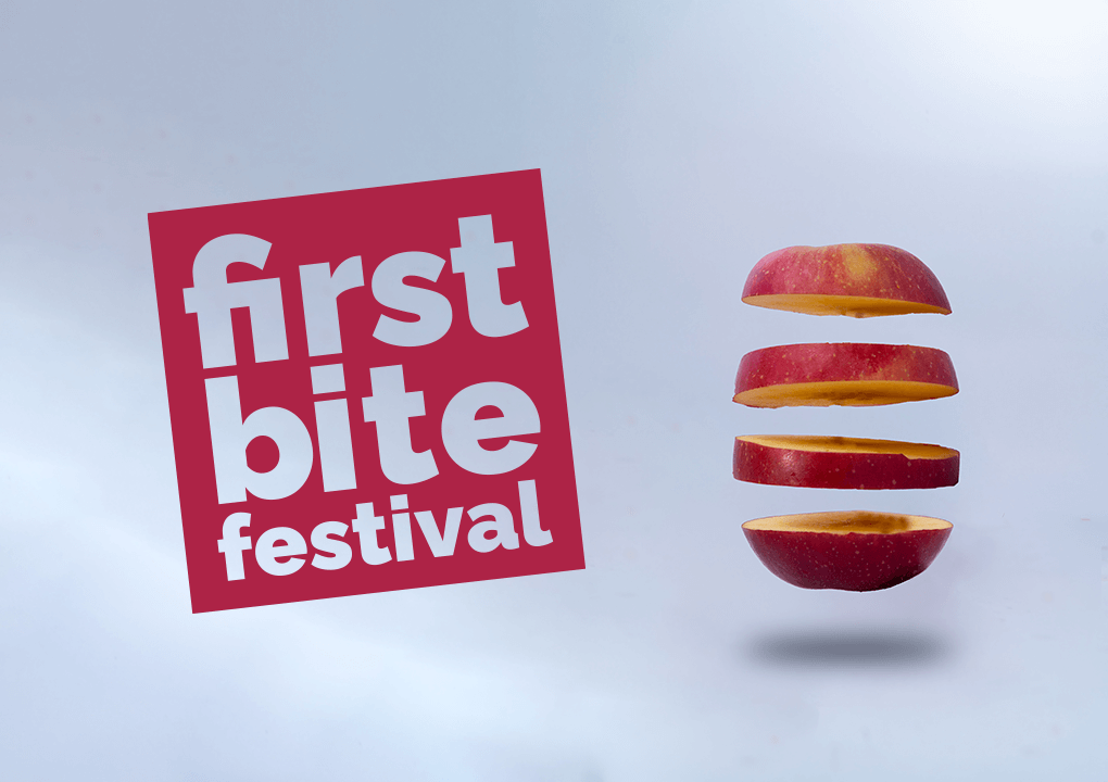 Cut out letters in a red square which read 'First Bite Festival' against a light grey background next to a segmented apple.