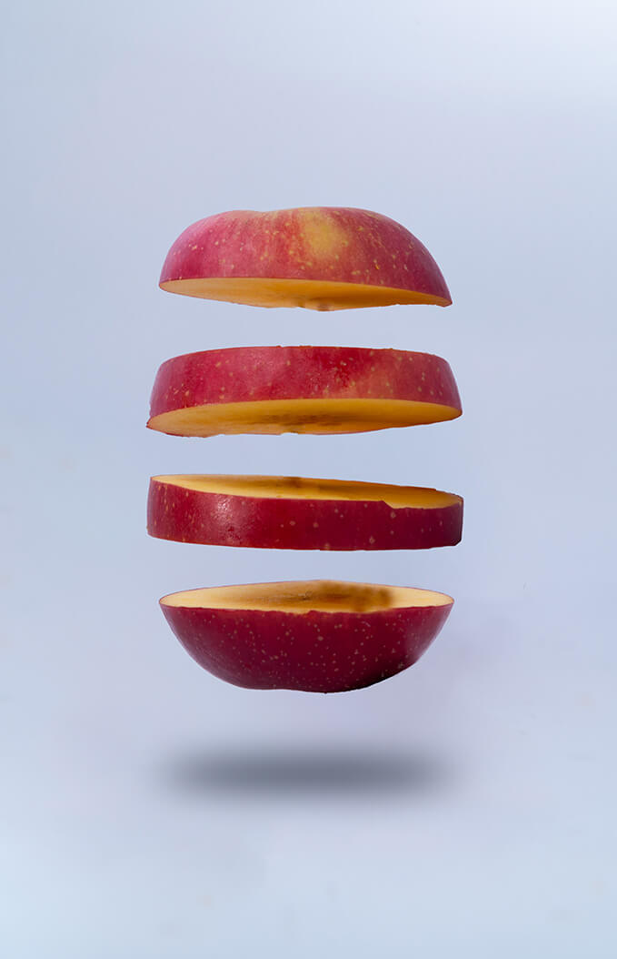 A segmented apple against a light grey background.