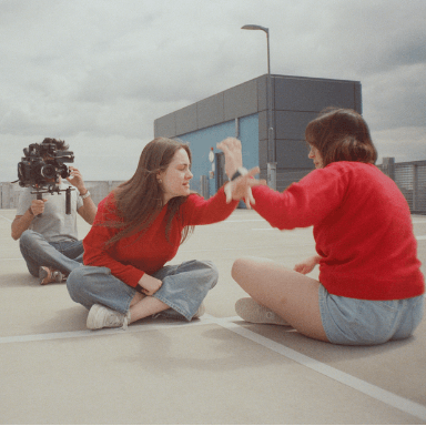 Two women sitting down facing each other in a car park making paper aeroplanes