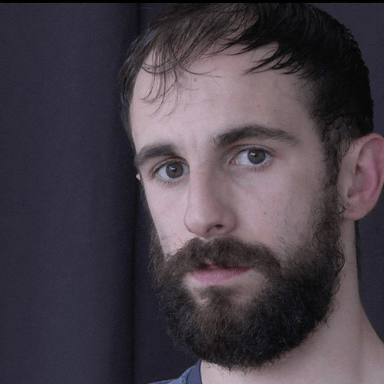 A bearded man looks directly at the camera