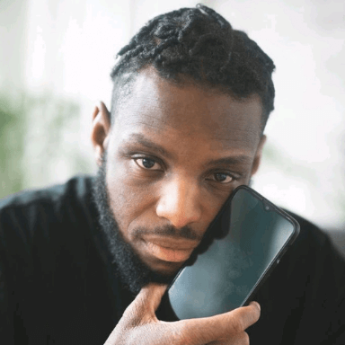 A man looks directly at the camera holding a phone to his face.