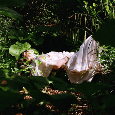 A person in a white dress lies on the ground surrounded by plants.