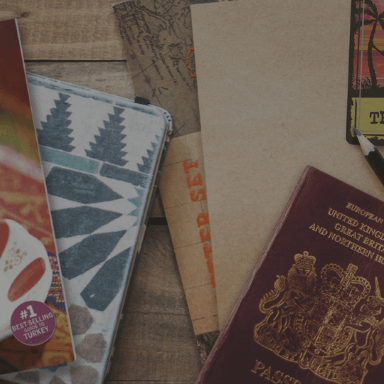 A passport, notebooks and magazines laid out and overlapping on a table.
