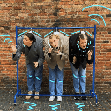 Three women inside suit jackets hanging on a clothes rail in front of a brick wall
