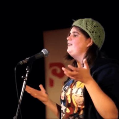 A person performing in front of a microphone, not looking towards the camera.