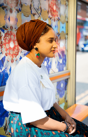 A side view of a woman wearing a head scarf, sitting at a bus stop.
