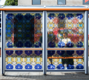 A bus stop decorated with a repeated patterned vinyl. A young woman can be seen through the pattern standing at the bus stop.