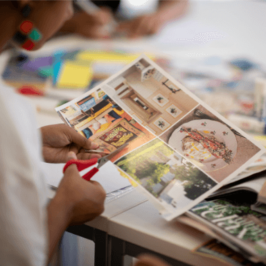 Close up of a person cutting out pictures from a magazine.