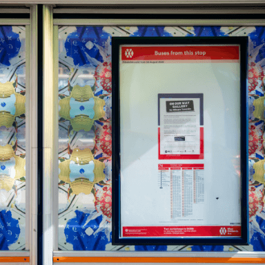 Close up of a bus stop decorated with a repeated patterned vinyl. The timetable sits within a plastic frame.